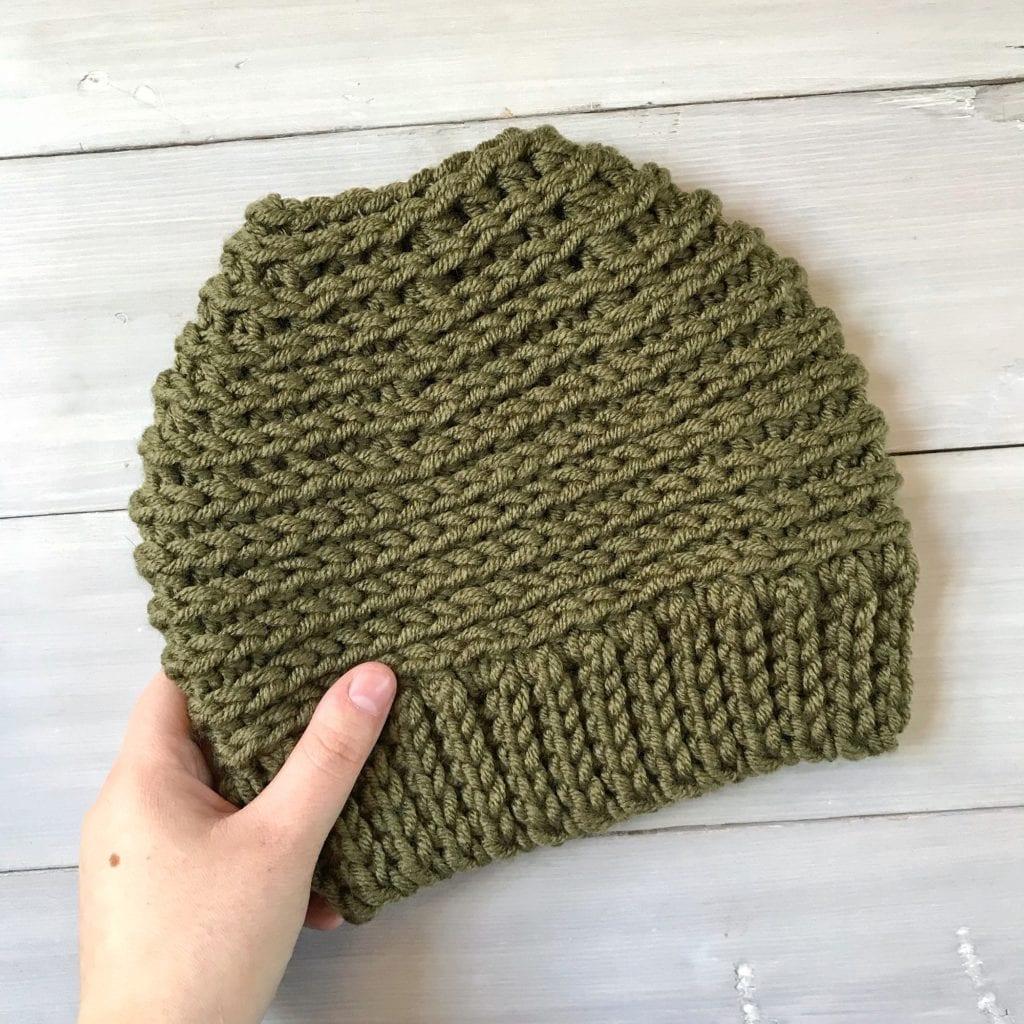 Hand holding an army green crochet messy bun hat