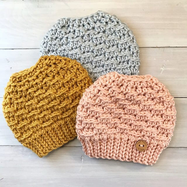 3 crocheted messy bun hats displayed flat