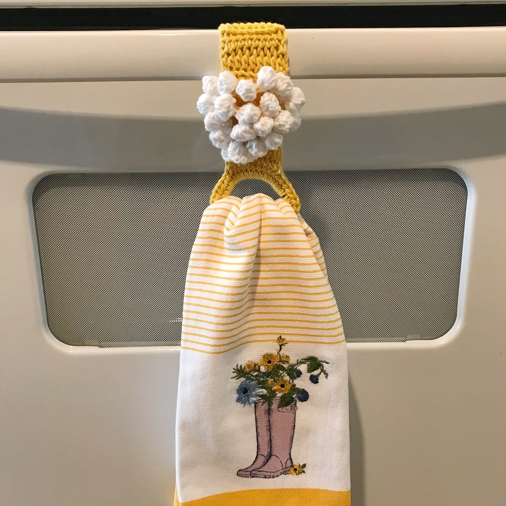 yellow and white crochet towel ring on a stove handle